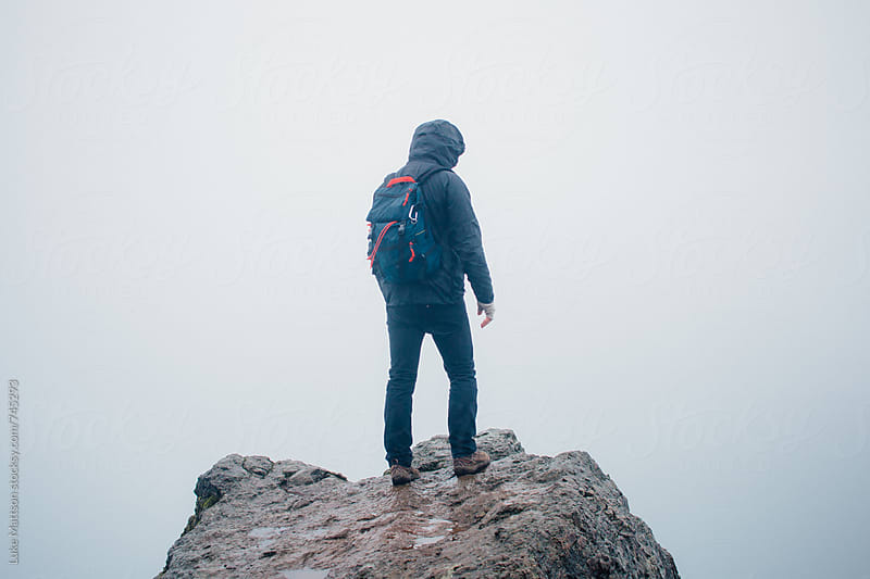 Hooded Hiker Wearing Backpack Stands On Rocky Ledge In Fog  by Luke Mattson for Stocksy United