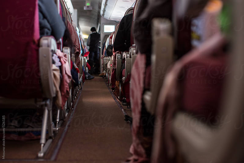 Aisle on a Crowded Airplane by Mosuno for Stocksy United