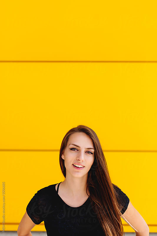Portrait of a beautiful woman on a yellow wall by MEM Studio for Stocksy United