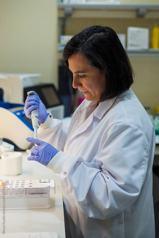 Female scientist using a pipette in a DNA laboratory by Bisual Studio for Stocksy United