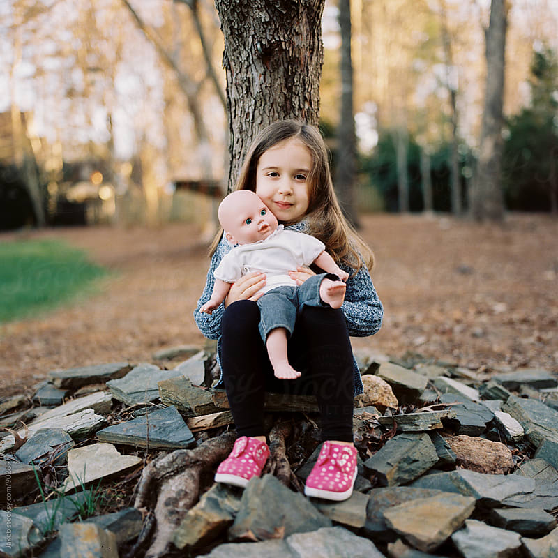 Beautiful young girl sitting by the foot of a tree playing with her doll by Jakob for Stocksy United