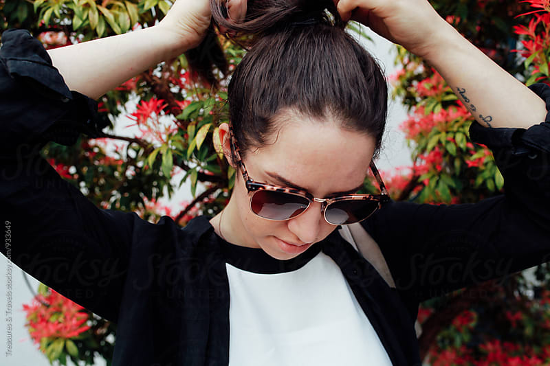 Woman wearing sunglasses doing her hair by Treasures & Travels for Stocksy United