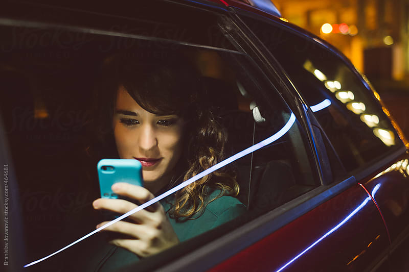 Woman sitting in the car and looking at the phone by Brkati Krokodil for Stocksy United