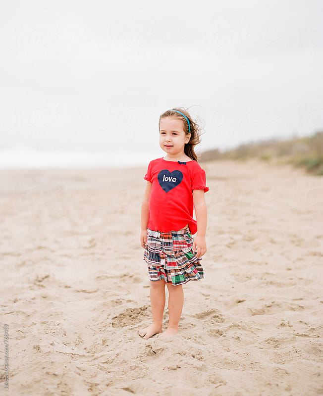 Beautiful young girl standing on a windy beach by Jakob for Stocksy United