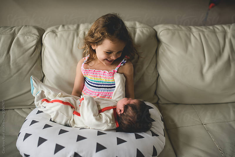 girl smiling at newborn baby by Courtney Rust for Stocksy United