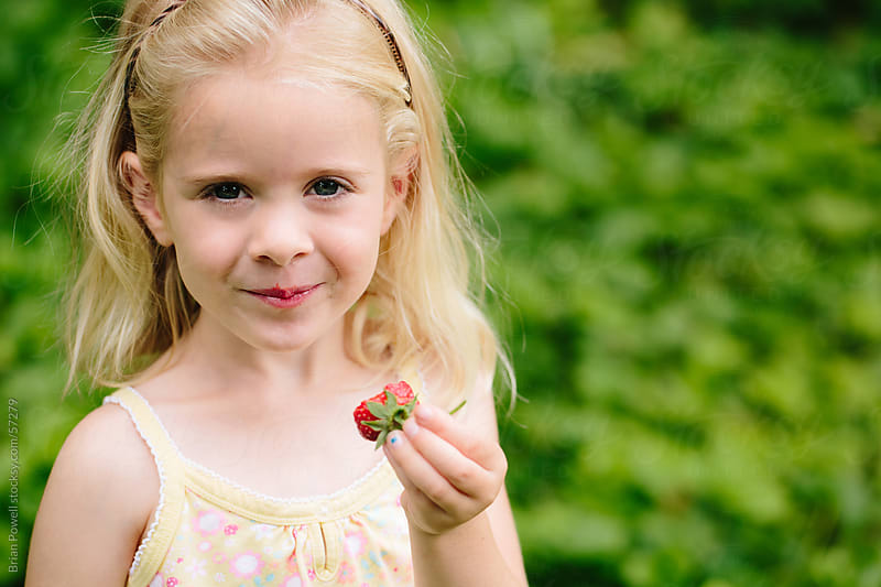 girl eating fresh picked strawberry by Brian Powell for Stocksy United