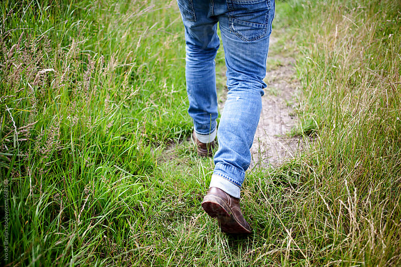Photo of a man's legs walking on a small path with grass on both sides by Ivo de Bruijn for Stocksy United
