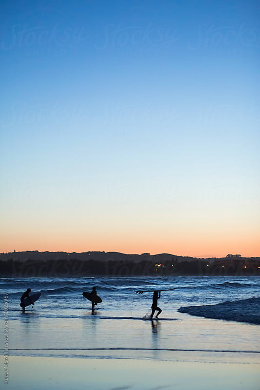 Three surfers walking into the waves by Reece McMillan for Stocksy United