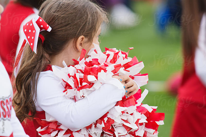 A young cheerleader watches the football game by Tana Teel for Stocksy United