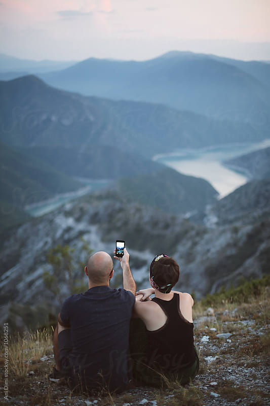 Couple enyoing at the mointain view and taking photos  by Ani Dimi for Stocksy United