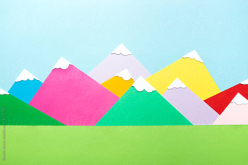 Green field in front of colorful paper mountains covered wth snow by Beatrix Boros for Stocksy United