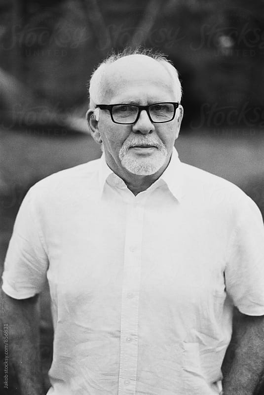 Portrait of a senior man in a white shirt and glasses by Jakob for Stocksy United