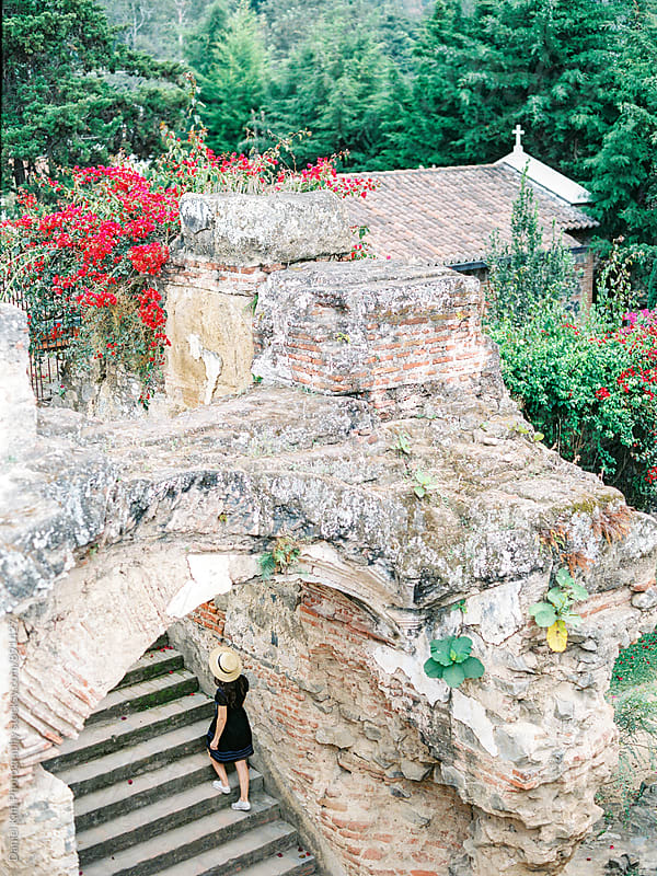 Woman walking up ancient ruin steps by Daniel Kim Photography for Stocksy United