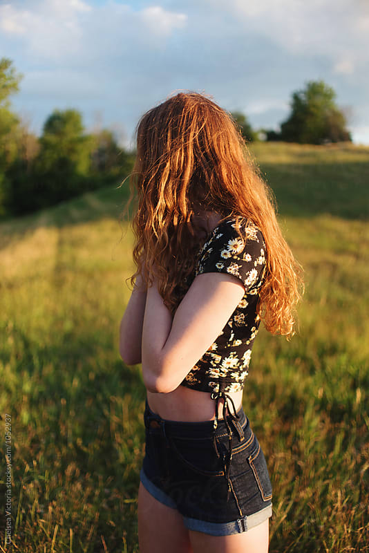 A teenage girl with red hair in the summertime by Chelsea Victoria for Stocksy United