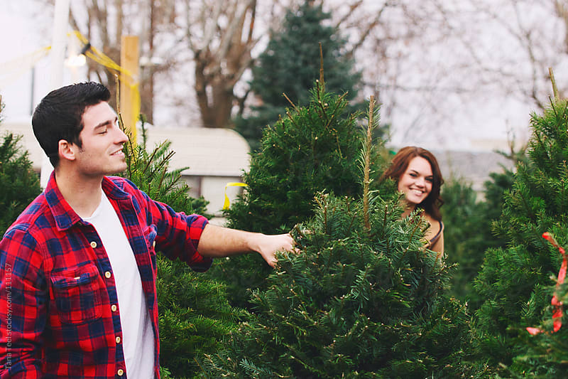 A young couple search for a Christmas tree together  by Tana Teel for Stocksy United