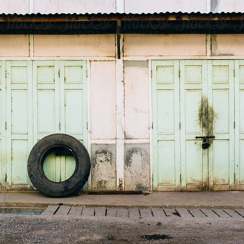 Tire Leaning Against Closed Shabby Wood Door by VISUALSPECTRUM for Stocksy United