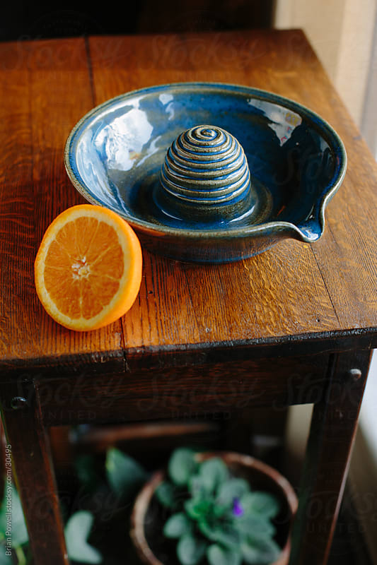 earthenware juicer and orange by Brian Powell for Stocksy United