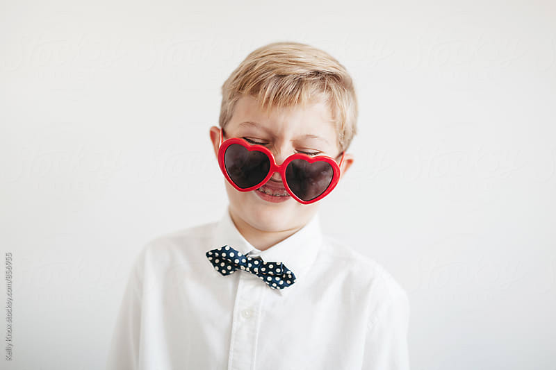 laughing boy wearing heart shaped sunglasses by Kelly Knox for Stocksy United
