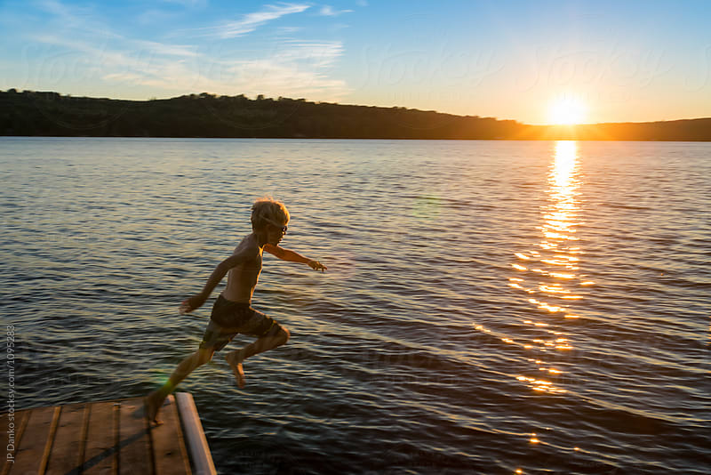 Boy Jumping Into Warm Summer Cottage Lake At Sunset from Dock by JP Danko for Stocksy United