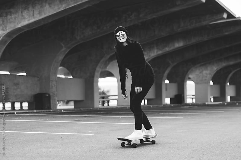Happy woman riding skateboard by Isaiah & Taylor Photography for Stocksy United