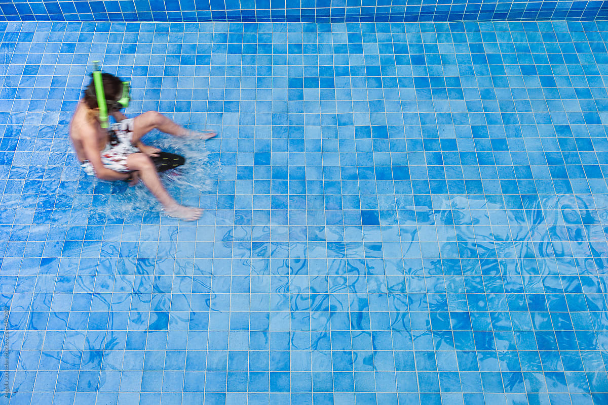 Stock Photo - Boy Having Fun On A Skateboard As A Blue Tiled Swimming Pool  Is Filling With Water