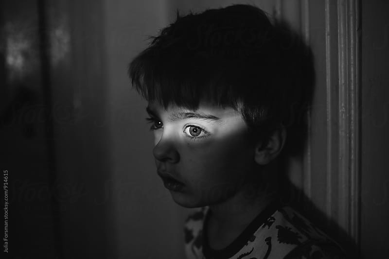 Black and white of boy in dark room with a bright strip of light across his eyes. by Julia Forsman for Stocksy United