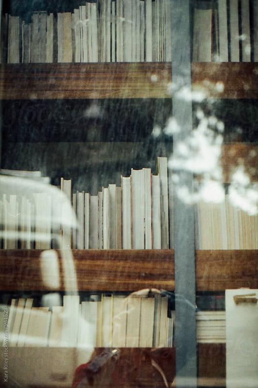 Bookshelves through glass window by Kara Riley for Stocksy United