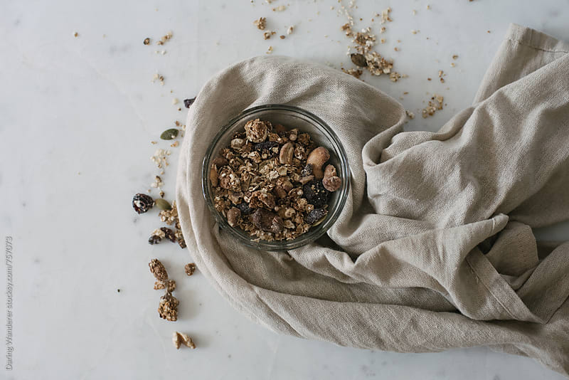 Homemade granola in a glass bowl on marble table background by Daring Wanderer for Stocksy United