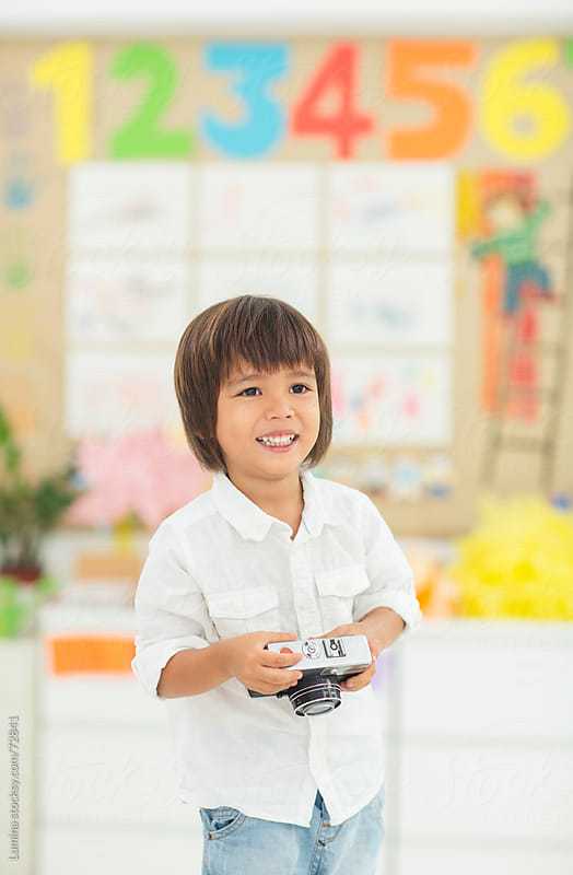 Cheerful Asian Boy Holding a Camera by Lumina for Stocksy United