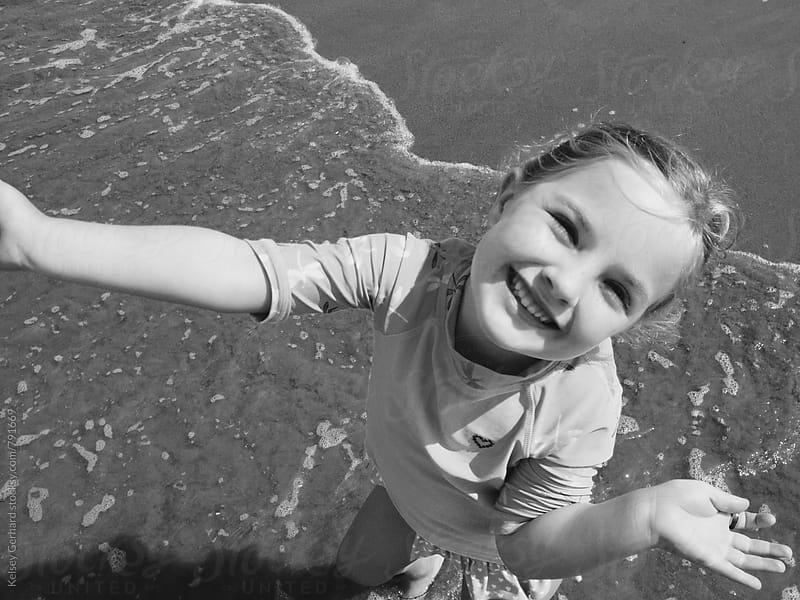 A little girl smiling up at the camera while playing in the ocean. by Kelsey Gerhard for Stocksy United