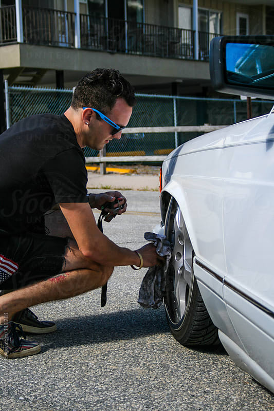 Hip young man clean the front wheels of his white car by Peyton Weikert for Stocksy United