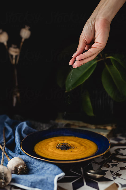 Sprinkling poppy seeds on pumpkin soup by Tatjana Ristanic for Stocksy United