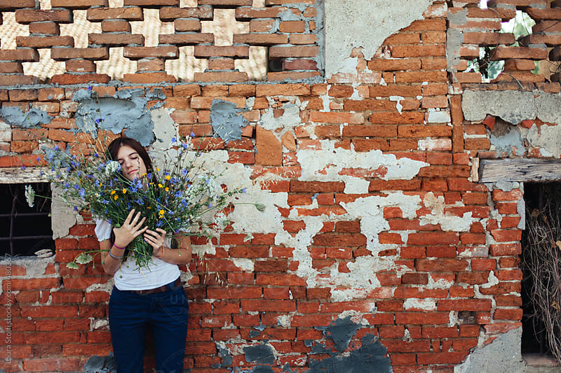 Pretty young woman stand with her head on flowers bouquet with eyes closed by Laura Stolfi for Stocksy United