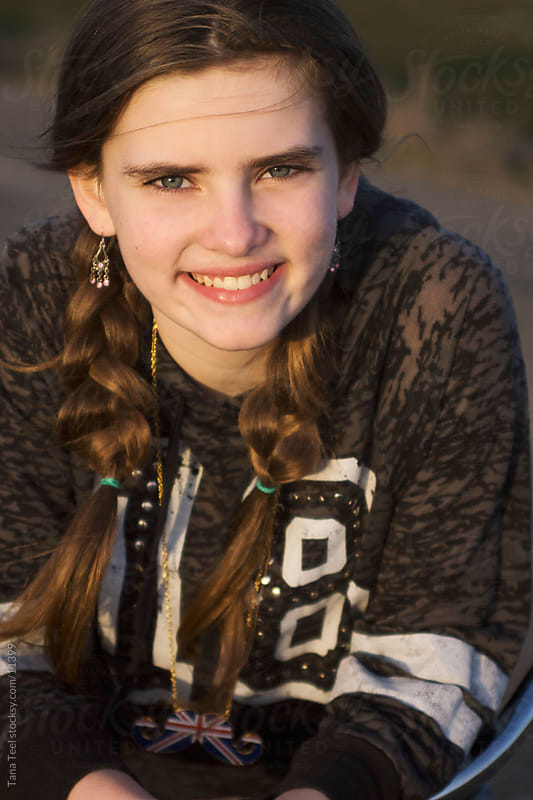 A young girl smiling into the sun. by Tana Teel for Stocksy United
