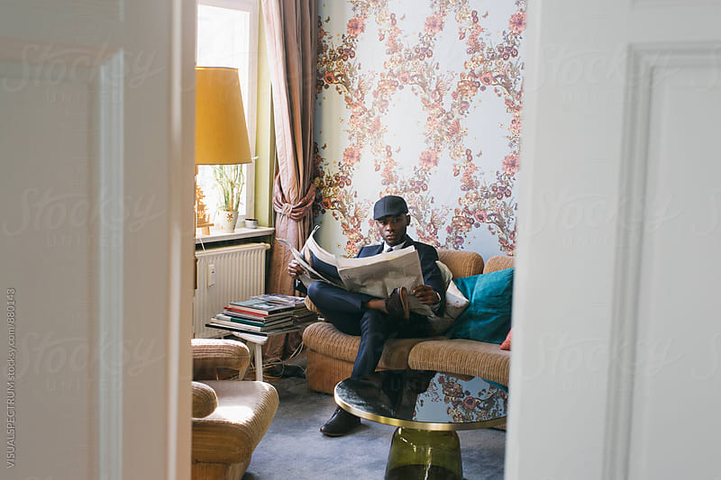 Stylish Young Black Man Reading Newspaper in Bright Living Room by VISUALSPECTRUM for Stocksy United