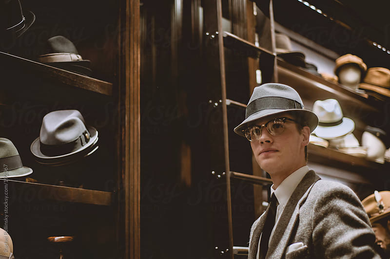 A dapper young man in a suit and tie tries on hats  by Rachel Bellinsky for Stocksy United