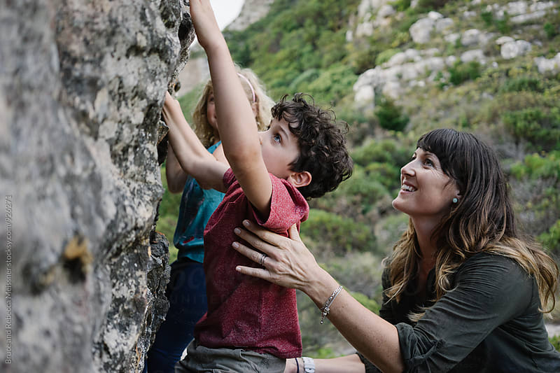 Mom and Kids rock Climbing by Bruce and Rebecca Meissner for Stocksy United