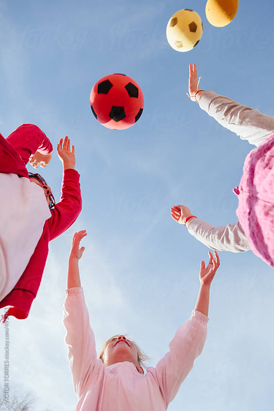 Little Girls in the Playground Throwing Balls to the Air by VICTOR TORRES for Stocksy United