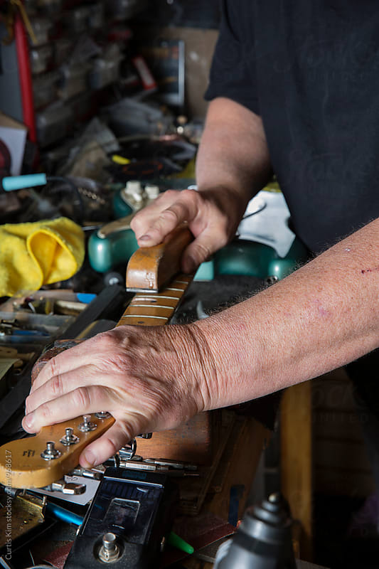 Guitar repair man working on guitar neck by Curtis Kim for Stocksy United