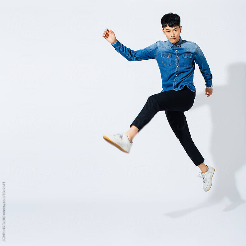 Young asian man jumping over white background.  by BONNINSTUDIO for Stocksy United