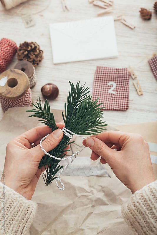DIY Christmas - Female Hands Tying Fir Twigs Together for Self-Made Xmas Gift by Julien L. Balmer for Stocksy United