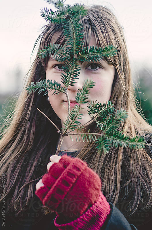 teen girl looking through branch of Christmas tree by Deirdre Malfatto for Stocksy United