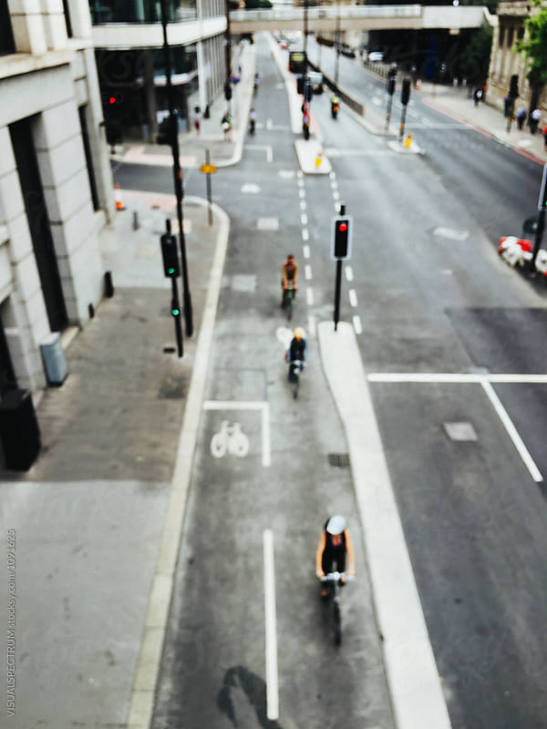 City of London - Defocused Overhead Shot of Cyclists Riding Through Inner City by Julien L. Balmer for Stocksy United