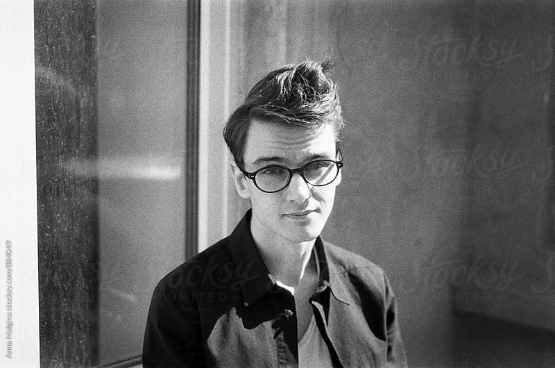 A black and white film portrait of a young beautiful man with eyeglasses looking at camera by Anna Malgina for Stocksy United