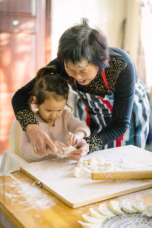 Grandmother and granddaughter making Chinese dumplings by Maa Hoo for Stocksy United
