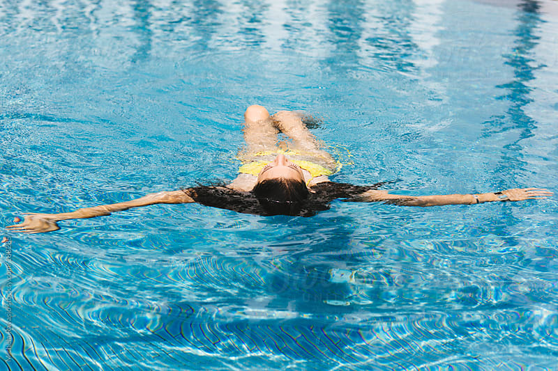 Young woman relaxing in the swimming pool by michela ravasio for Stocksy United