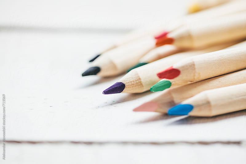 Set of colorful pencils against a white wooden background by Aleksandar Novoselski for Stocksy United