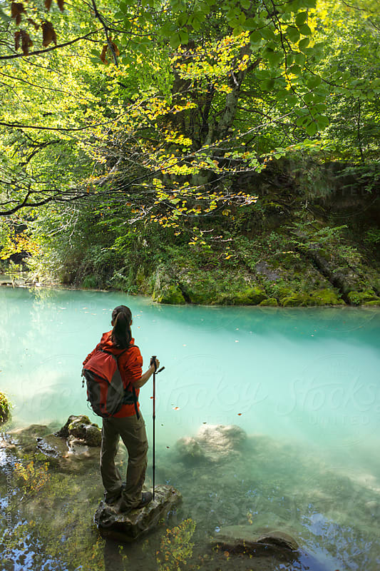 Woman hiker with backpack looking at a beautiful river by ACALU Studio for Stocksy United