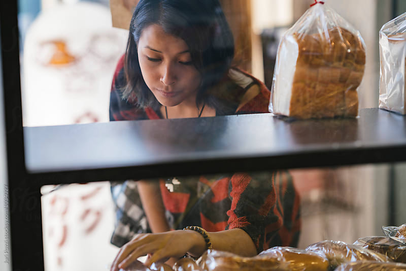 Young asian woman buying bread in a bakery  by Juri Pozzi for Stocksy United