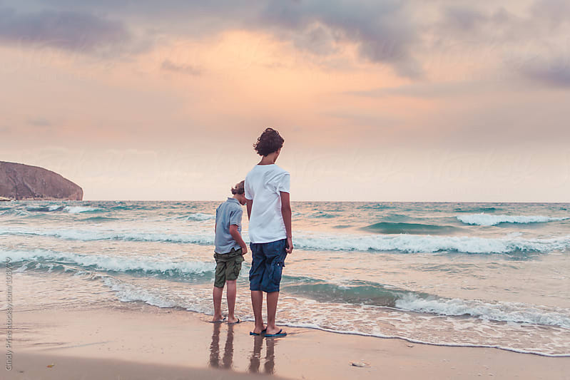 Two brothers standing at the shoreline on the beach at sunset in the summer by Cindy Prins for Stocksy United